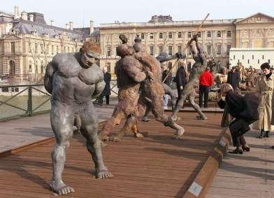 des touristes et des parisiens regardent, le 19 mars 1999 sur le pont des Arts à Paris, les saisissantes sculptures du Sénégalais Ousmane Sow, intsallées jusqu'au 20 mai et qui devraient être inaugurées, ce soir par le ministre de la Culture Catherine Trautmann et le maire de Paris, Jean Tiberi. Soixante-huit oeuvres monumentales - lutteurs Noubas, guerriers Masaïs pasteurs Peuls, témoignent de la puissance d'expression d'un artiste considéré comme un des plus grands sculpteurs contemporains. (IMAGE ELECTRONIQUE) Tourists and residents look at some of the sculptures by Senegalese sculptor Ousmane Sow exhibited on the famous Ponts des Arts 18 March 1999 in Paris. The exhibition, due to be officially inaugurated later 18 March 1999, is scheduled to last for two months. The some 70 works include naked Nouba wrestlers, Peul shepherds, Massai and Zulu warriors. (ELECTRONIC IMAGE) AFP PHOTO AFP/ALEXANDER JOE/ao / AFP PHOTO / ALEXANDER JOE